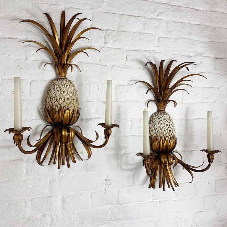 Stunning pair of gilt tole ware pineapple wall sconce's Italian circa 1950s-1960s The central pineapple is metal and in cream color with gold highlights The fronds are large and full The lights have 2 bulb holders each, they take a small E10
