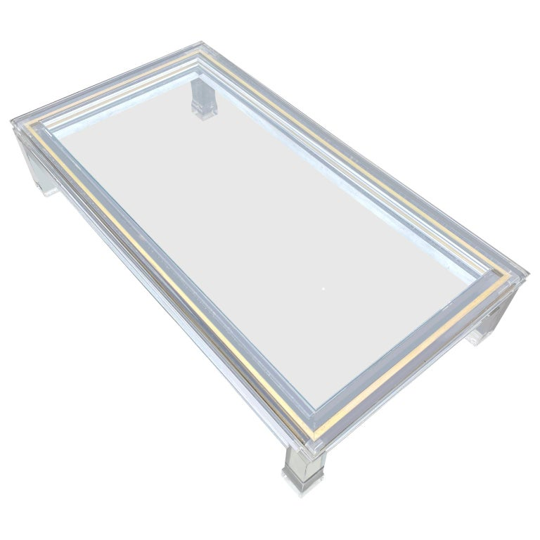 Large Italian rectangular Lucite, inlaid brass edge and glass coffee table  The coffee table has a large shadow box, that is accessible by lifting the top glass piece off. Could be decorated with all kind of accessories, leaves, acorns, sand,