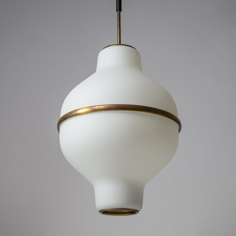 Superb Italian satin glass chandelier from the 1950s, designed by Oscar Torlasco for Lumi Milano (original manufacturers label on top). Two large tapered blown glass diffusers with a satin finish and a thick brass