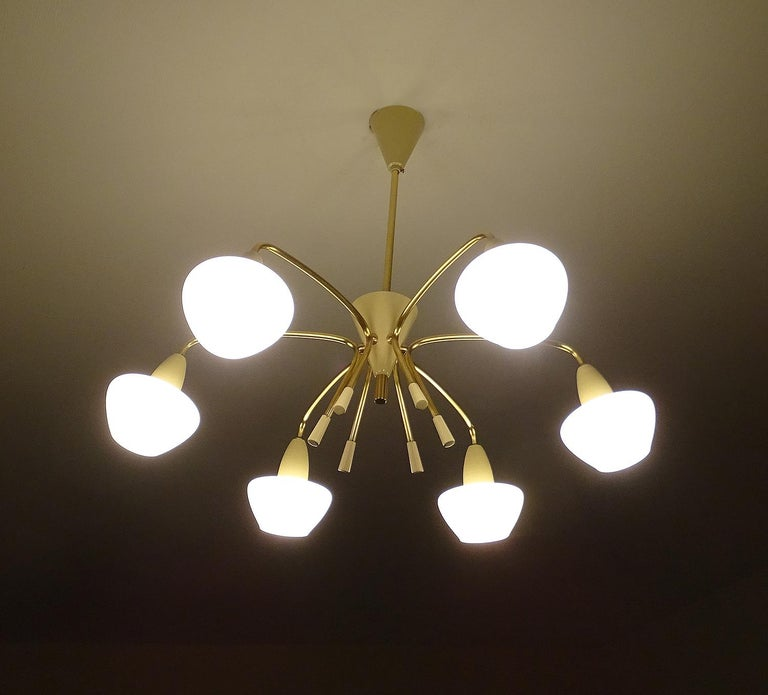 Large 1960s chandelier in the manner of Stilnovo, curved arms which forms a circular array in the middle, brass with egg white enamel trim, opaline glass diffusers. Dimensions: H 21.26 in. x Dm 24.41 in. H 54 cm x Dm 62 cm Six candelabra size bulbs,