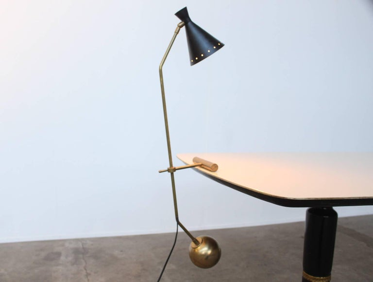 Beautiful elegant counter weight desk or table lamp identical to Stilnovo. The lamp balances and swings freely on the table edge by means of the weight of the solid brass counter balance ball. The lamp is height adjustable and the shade is in