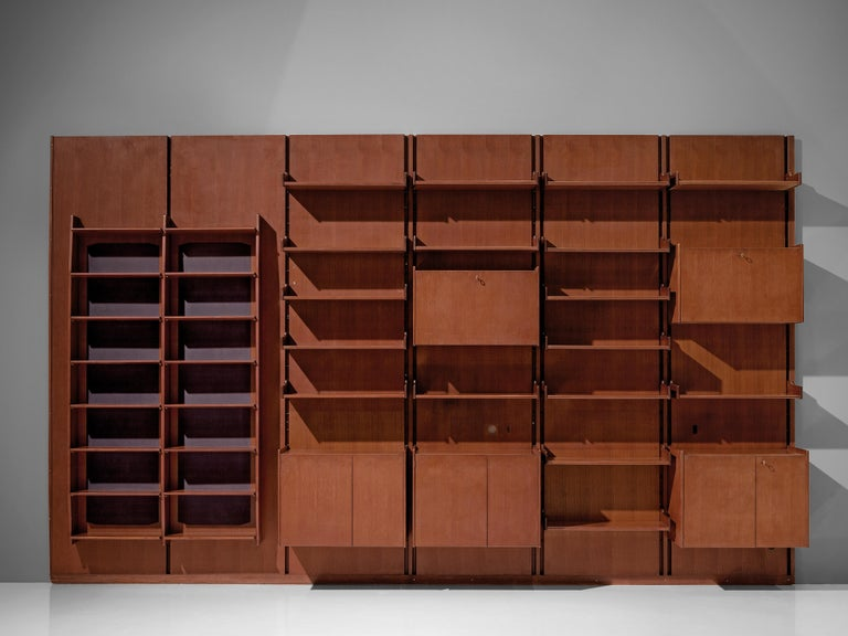 Italian wall unit, teak, brass, metal, Italy, 1950s.  This large wall unit offers a variety of use. The unit consists of six panels with various storage facilities. Multiple shelves, five cabinets with different interior structure and two columns of