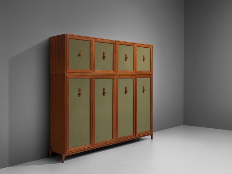 Italian wardrobe, teak, green fabric, brass, Italy, 1950s.  This wardrobe has a very distinguished design that is characterized by the combination of teak wood and green fabric that is tightened over the front doors. Geometric handles are on the