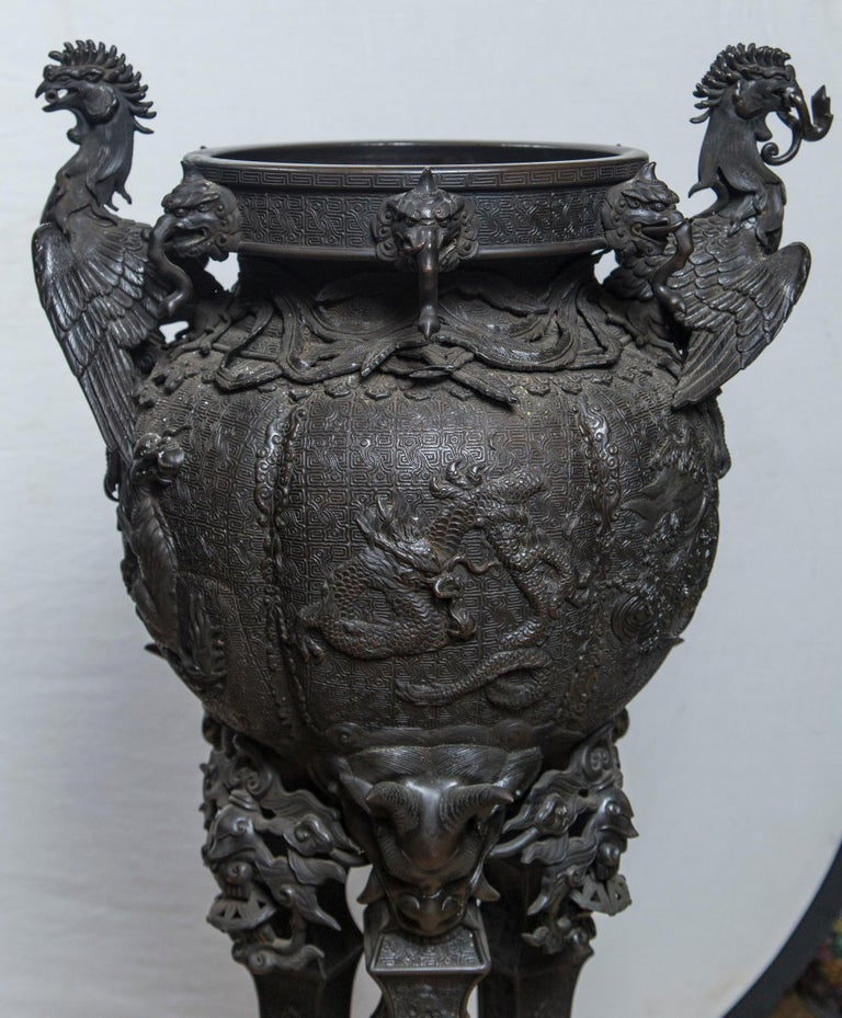 Dating from the Meiji period this standing koro or  incense  burner has a circular stepped base. Three legs topped with horned and other demons standing on upside down foo dogs. Elephant heads on the rim and phoenix birds, wing spread, upper