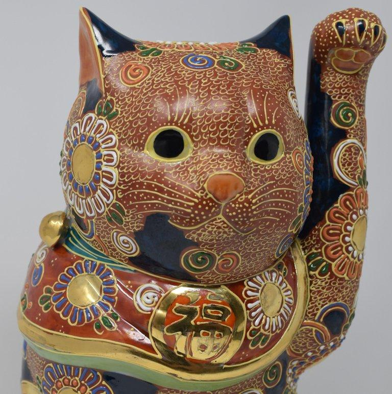 "Large Japanese contemporary beckoning cat, a gilded and hand painted porcelain piece from the Kutani region of Japan. The cat is adorned with multiple golden medallions and is covered with raised loops characteristic of the Kutani ""moriage"" style."