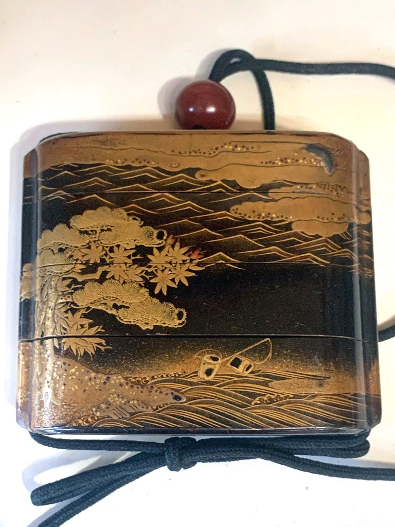 A Japanese four-case inro with string and an amber bead ojime of Meiji period circa 19th century. The relatively large inro has a black lacquered background with fine detailed gold hiramaki-e decoration. On one side, a cluster of three huts stand