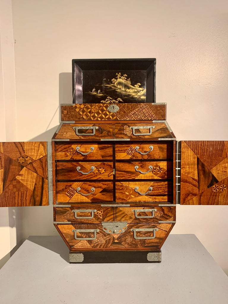 A fine and unusually large Japanese table cabinet or jewelry chest with yosegi marquetry work and lacquer paneled doors, Meiji period, late 19th century, Japan.   The oversized table cabinet of irregular octagon shape, with a lift top featuring a