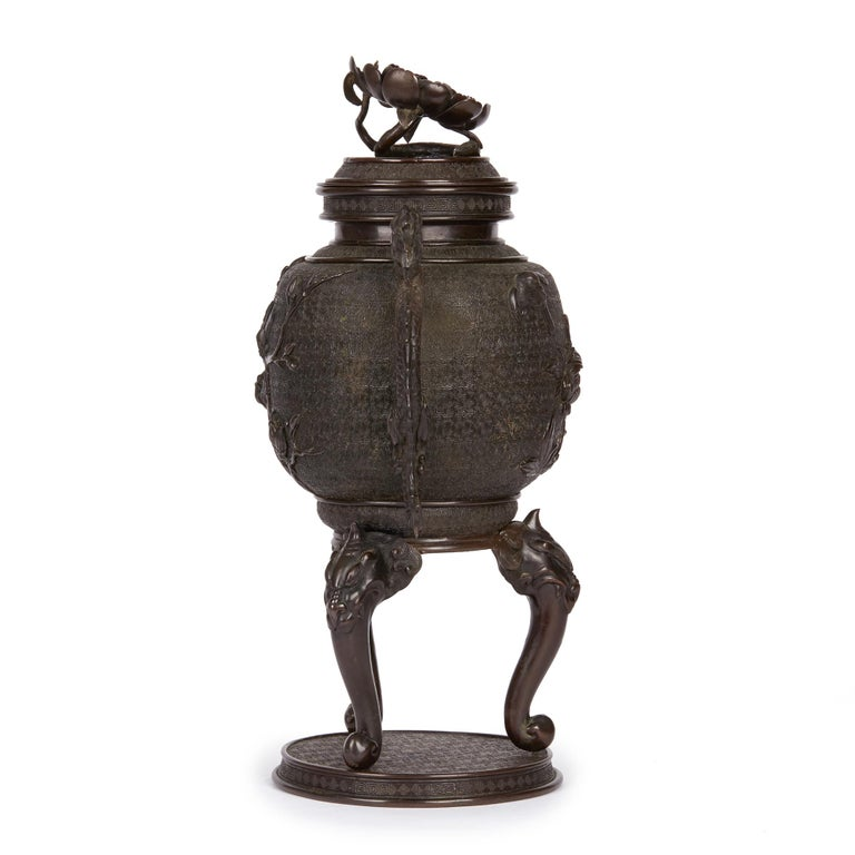 A large and stylish antique Japanese Meiji bronze lidded twin handle urn standing on a rounded plinth base with tongue and grotesque head formed legs with dragon handles and a flat cover with a large prunus flower head terminal. The body of the urn