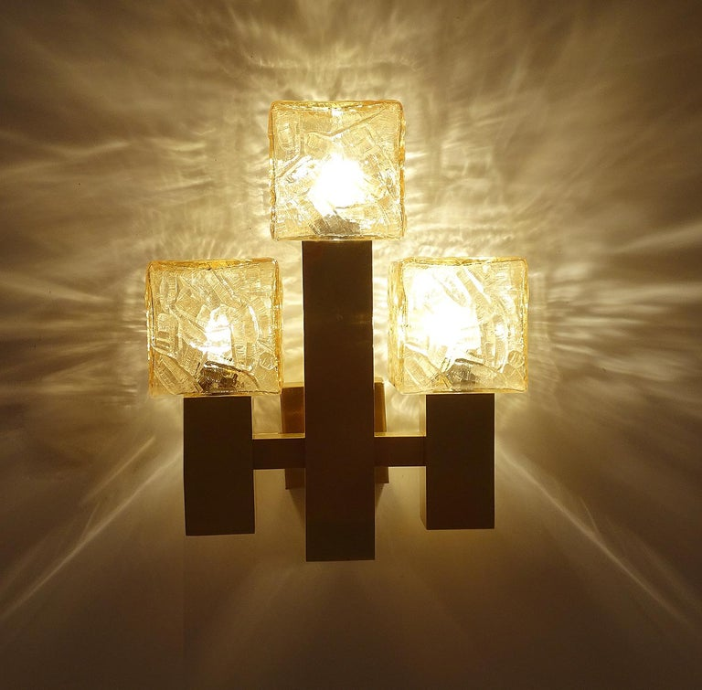 Large Kalmar sconce, featuring 3 structured cubic glass shades with a light amber tint, cruciform brass structure  Dimensions: H 14.18 in. x W 11.42 in. x D 5.32 in. H 36 cm x W 29 cm x D 13.5 cm Three candelabra size bulbs 40 watts.
