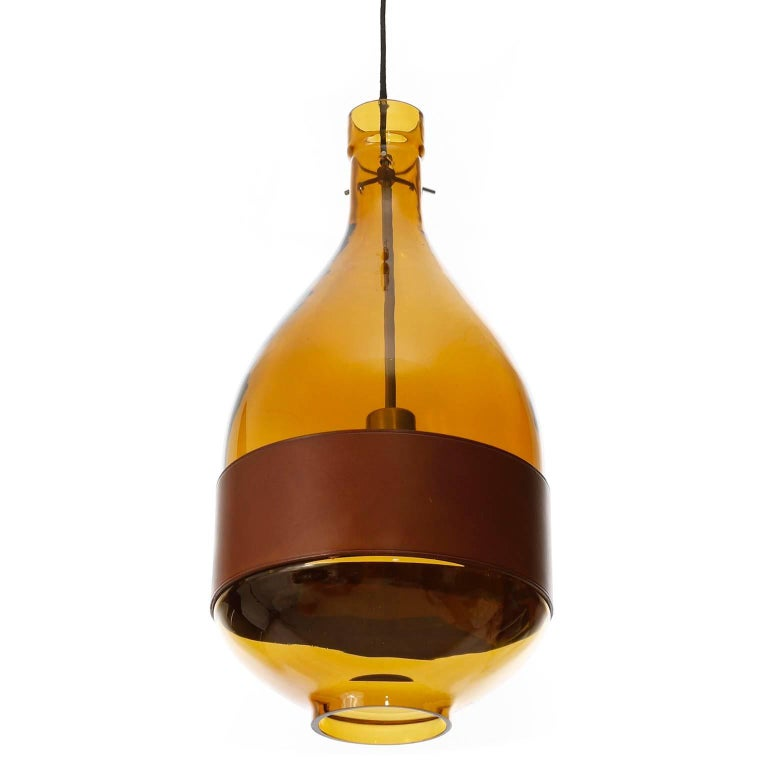 A beautiful glass pendant light fixture by Kalmar, manufactured in Mid-Century, circa 1970 (late 1960s or early 1970s).  It is made of an hand blown amber toned glass body with a belt made of brown leather. The dimensions of the glass body without
