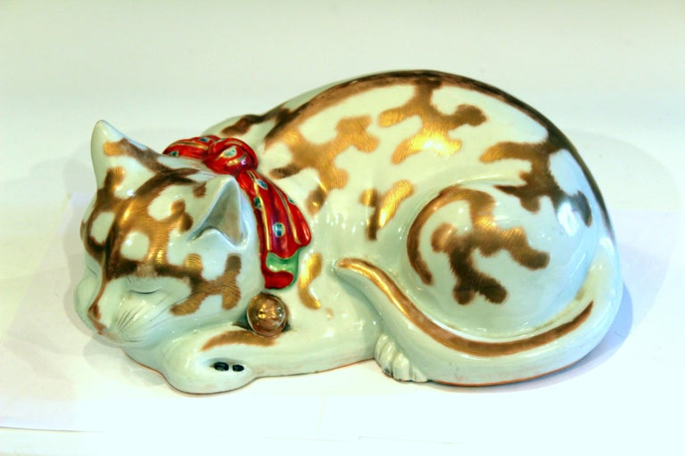Japanese Kutani porcelain cat figure peacefully curled in sleep with finely painted detail, gilt highlights, and bright red bow, circa 1920s. Large life like size. Export stamp on base. Measures: 13