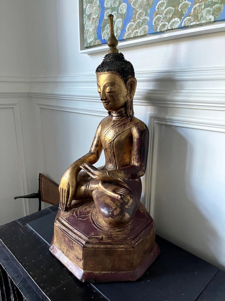 A gilt and lacquered wood Buddha statue from Southeast Asia likely Burma, circa 19th century. The Buddha is depicted as seating on a slightly tapered multifaceted plinth throne in an