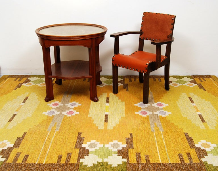 A large flat-weave rölakan carpet designed by Ingegerd Silow, Sweden. Handwoven with a geometric pattern where the colors are different shades of yellow, brown, green, pink and light blue-purple. Signed IS in the right hand corner. Professionally