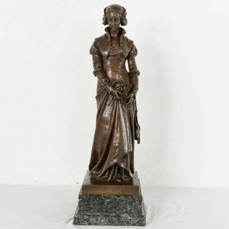 """Standing at an impressive 32 inches in height, this late 19th century bronze statue on a green marble base entitled """"Marguerite"""" features a woman with bowed head in Renaissance dress. Her hands carry a prayer book with a clasp, and rest gently at"""