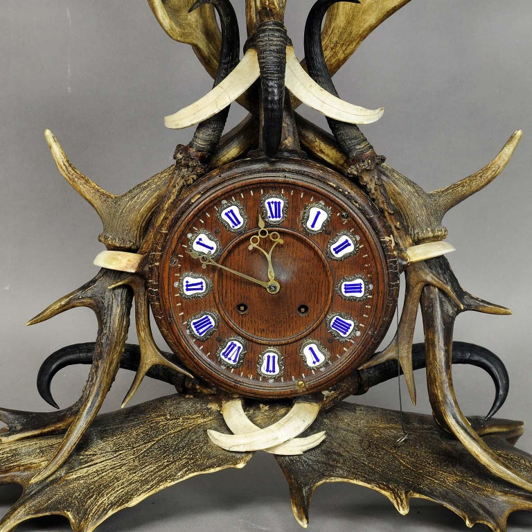 A rare antique lodge style mantel clock. oakwood case, richly decorated with antlers from the deer and fallow deer, mountain goat horns and wildboar tusks. 8-day clockwork in working order, revised by an clockmaker. Executed circa 1900.  Measures: