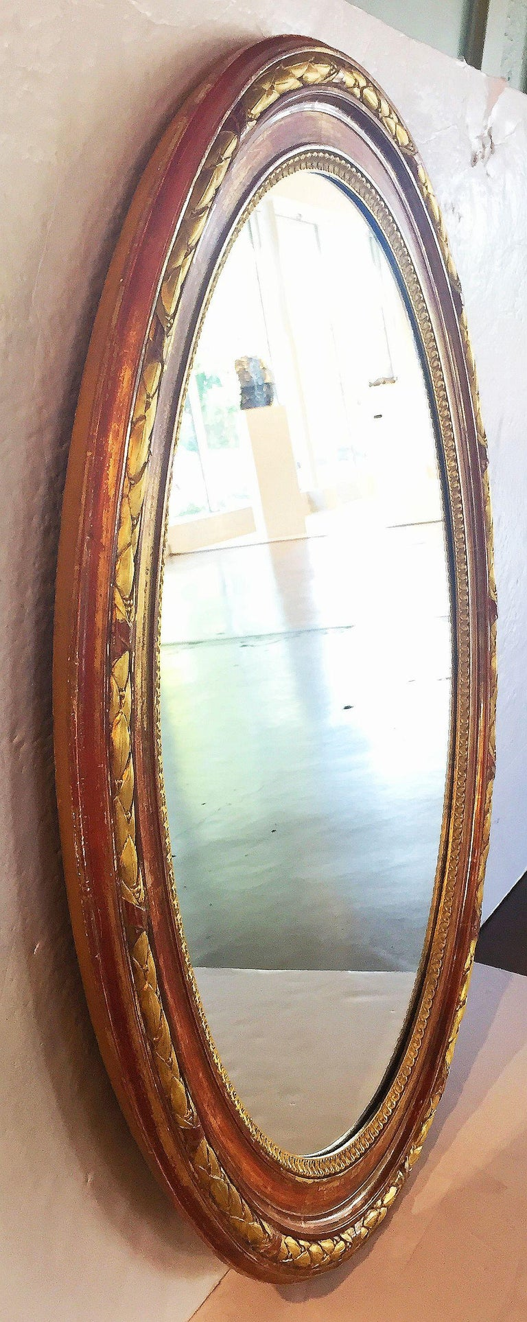 A fine large Louis Philippe oval gilt mirror from France, featuring a raised laurel leaf with ribbon design around the circumference.  Dimensions are: H 45 3/4 inches x W 36 3/4 inches x D 2 1/2 inches.