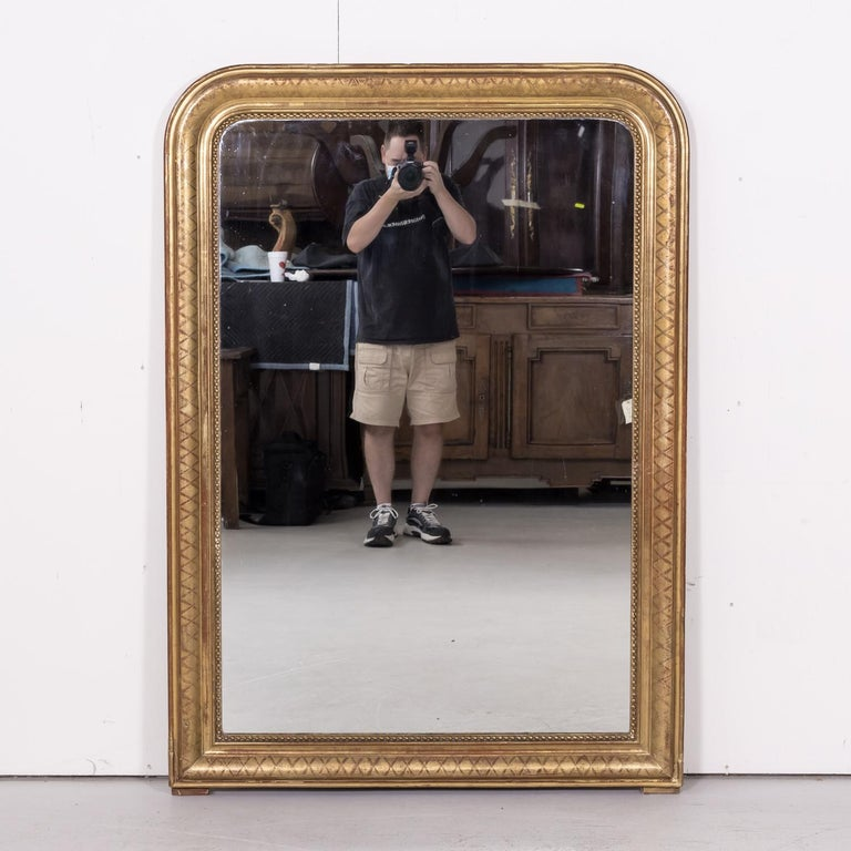 A large 19th century French Louis Philippe period giltwood mirror having its original mercury glass and cross hatch etching to the frame, circa 1840s. The tall rectangular shape of the frame has straight corners at the base, while the upper