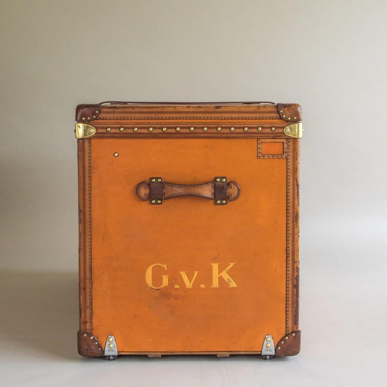 A splendid taller Louis Vuitton steamer trunk in orange Vuittonite (coated canvas) with leather trim to the edges, brass fittings, leather handles and original cotton lining to the interior. It even has the original leather strap around the middle