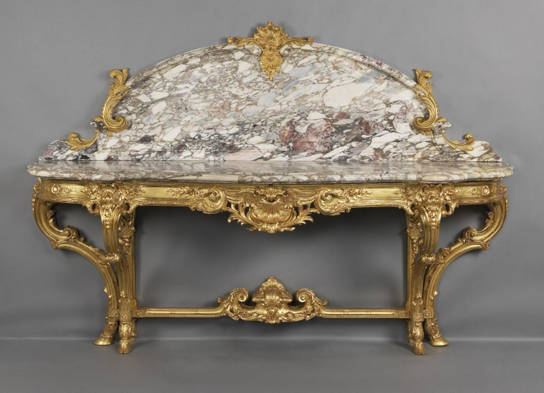 A large and impressive Louis XV style carved giltwood and gilt bronze mounted console table with a Fleur de Pêcher marble top and back panel, by Wandenberg.   French, circa 1880.  Stamped to the carcass 'WANDENBERG DOREUR, PARIS'.   This