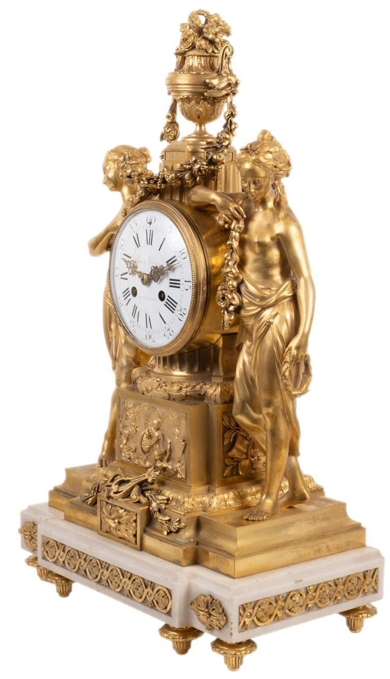 A Fine quality French 19th century gilded ormolu and white marble mantel clock in the Louis XVI style. Having a two handled urn to the top with flowers and garlands draping down to two semi nude classical female figures either side of the white