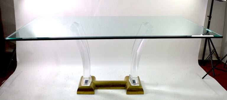 Wonderful Lucite and brass based glass top dining table by Jeffrey Bigelow. Exuberant 1980's Art Deco Revival, Hollywood Regency style in original, clean ready to use condition. The brass base shows patination, normal and consistent with age. The