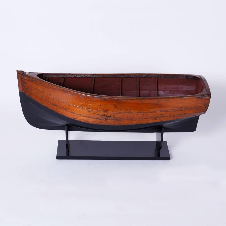 Inspired model of a boat or skiff expertly crafted in mahogany, probably by a boat builder, having a graceful form and has acquired a well earned patina only time can give.