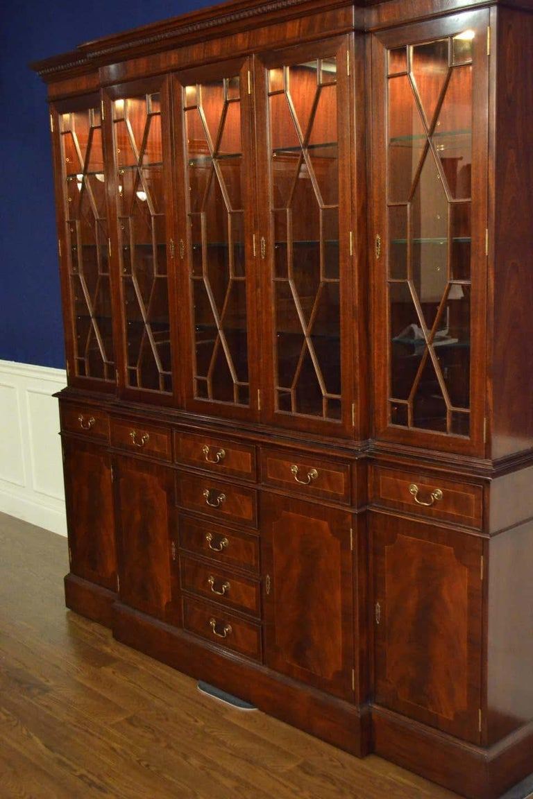 This is a large traditional mahogany breakfront bookcase or china cabinet with five doors by Leighton Hall. It features four bottom doors and nine drawers with swirly crotch mahogany fields and straight grain mahogany borders. The top doors feature