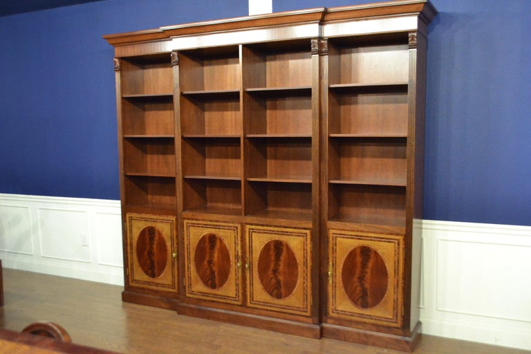 This is made-to-order traditional mahogany bookcase with four doors made in the Leighton Hall shop. It features four doors with swirly crotch mahogany fields and satinwood and santos rosewood borders. The corner posts are fluted with carvings at the