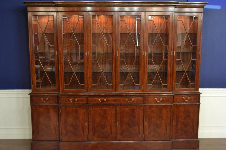 This is the ultimate large traditional mahogany breakfront bookcase or china cabinet with six doors by Leighton Hall. It features six bottom doors and drawers with swirly crotch mahogany fields and straight grain mahogany borders. The top doors