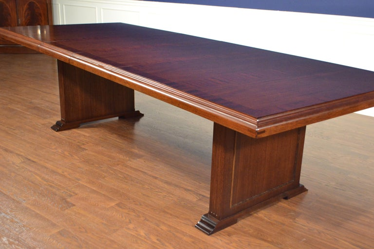 This is a made-to-order mahogany conference table made in the Leighton Hall shop. It features a field of cathedral mahogany with a straight grain mahogany border and a solid mahogany edge. It has two