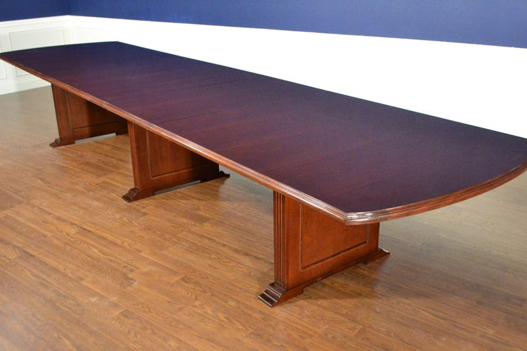 This is a made-to-order mahogany conference table made in the Leighton Hall shop. It features a field of cathedral mahogany with an Ogee-shaped solid mahogany edge. It has three