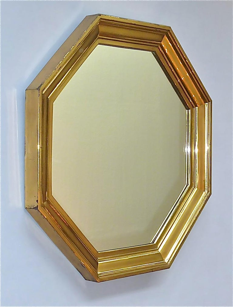 Fantastic large octagonal Maison Jansen mirror, France, around 1970s. Probably designed by Sandro Petti or Guy Lefevre the beautiful mirror has an octagonal shape made of a stepped patinated brass frame with mirror glass on a wood base. The high