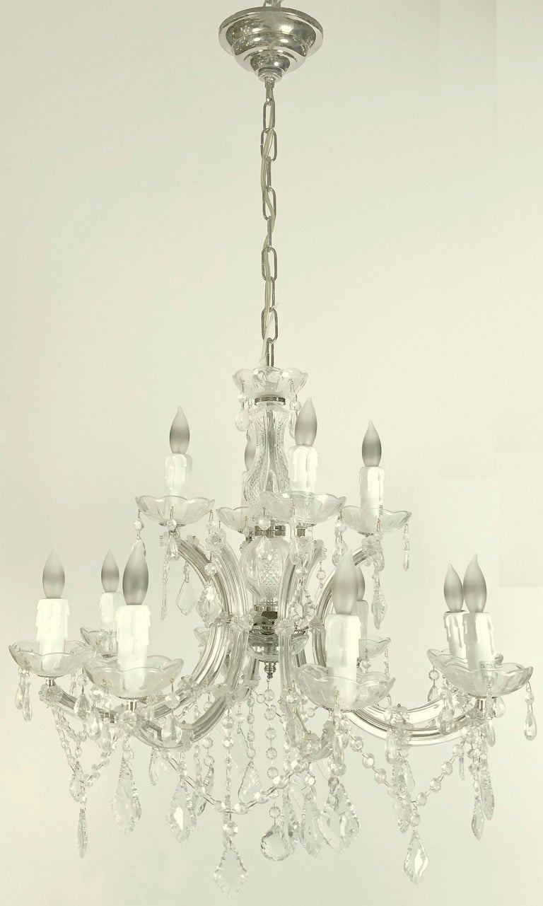 A lovely large Maria Theresa twelve-light chandelier (or hanging fixture) of crystal, glass and chromed metal featuring serpentine arms, each candle light with dangling pendants and decorative bobeche.  Measures: 24 inches diameter.  U.S.-wired