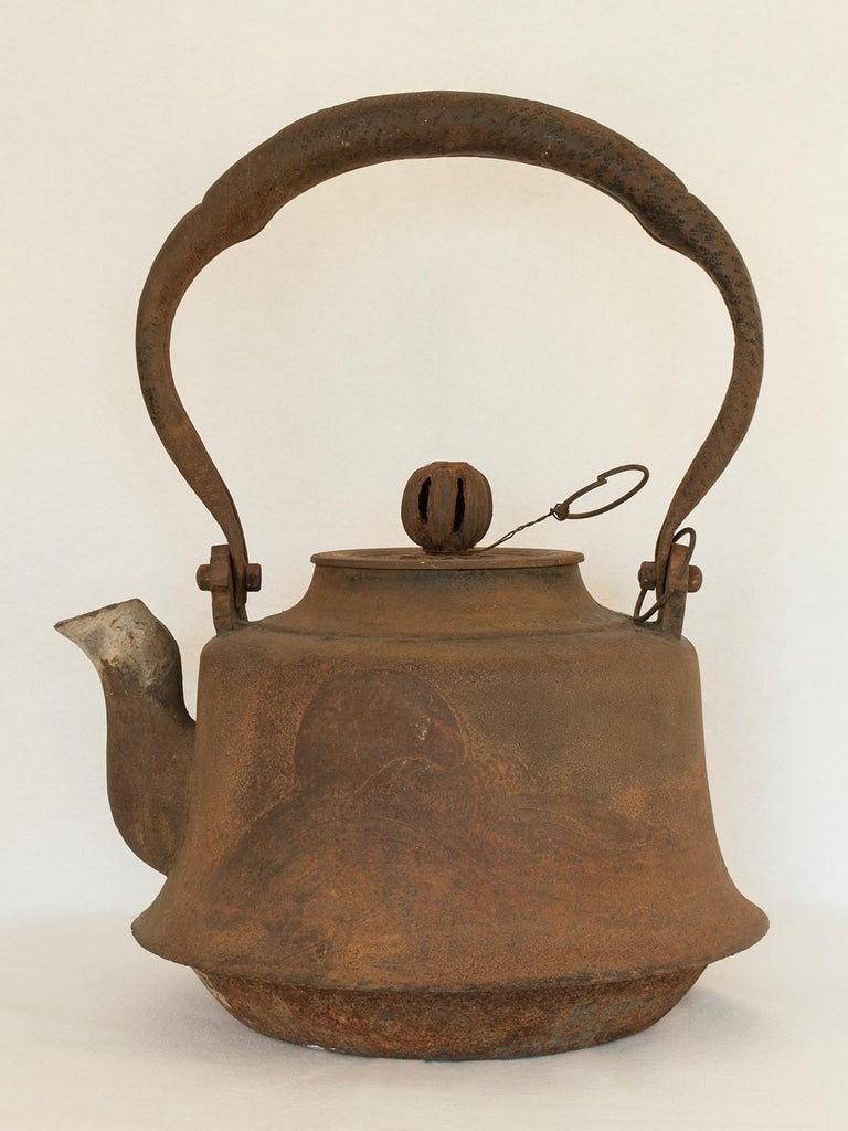 Large Meiji Period Iron Tea Pot, Japan  This very large iron tea pot would have been used outdoors to heat water over a large fire. There is a flying crane depicted on one side and a celestial body, perhaps the moon, setting in a wave-filled sea on