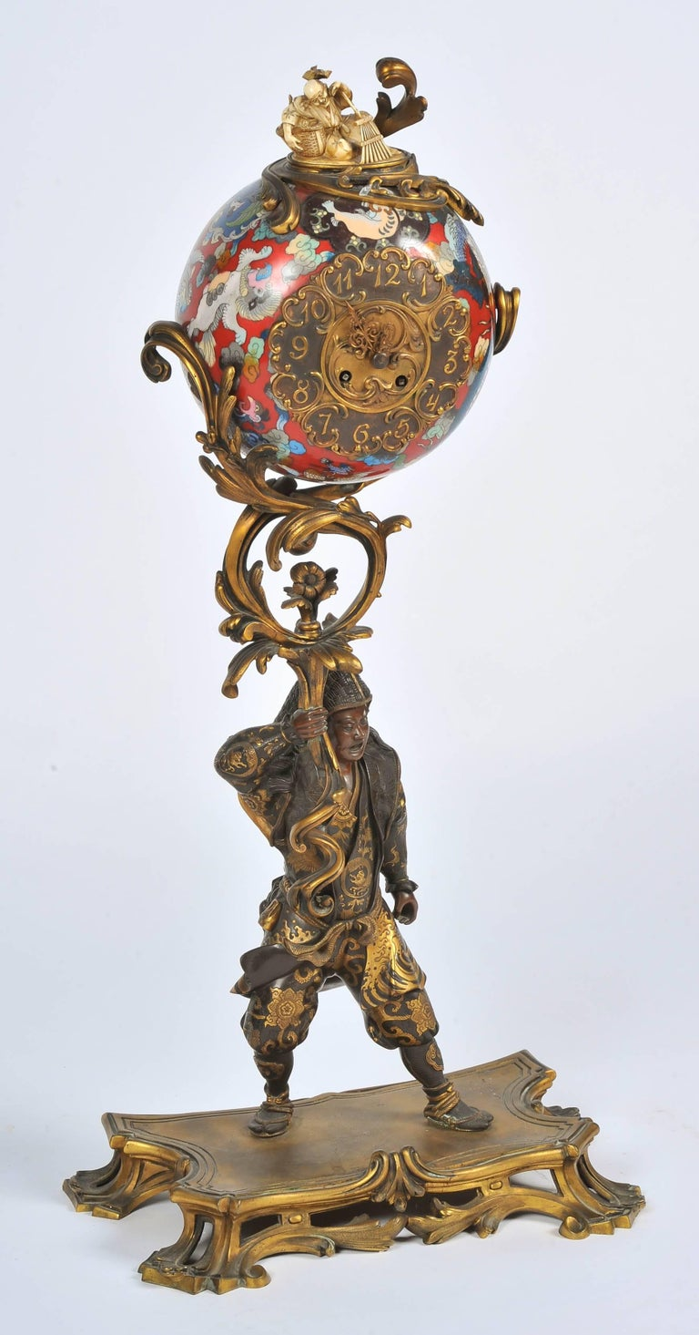 A fine quality Japanese Meiji period (1868-1912) bronze warrior with gilded highlights, holding aloft a Cloisonné enamel ball, depicting wonderful mythical creature in bold colours with an inset eight day duration clock that chimes on the