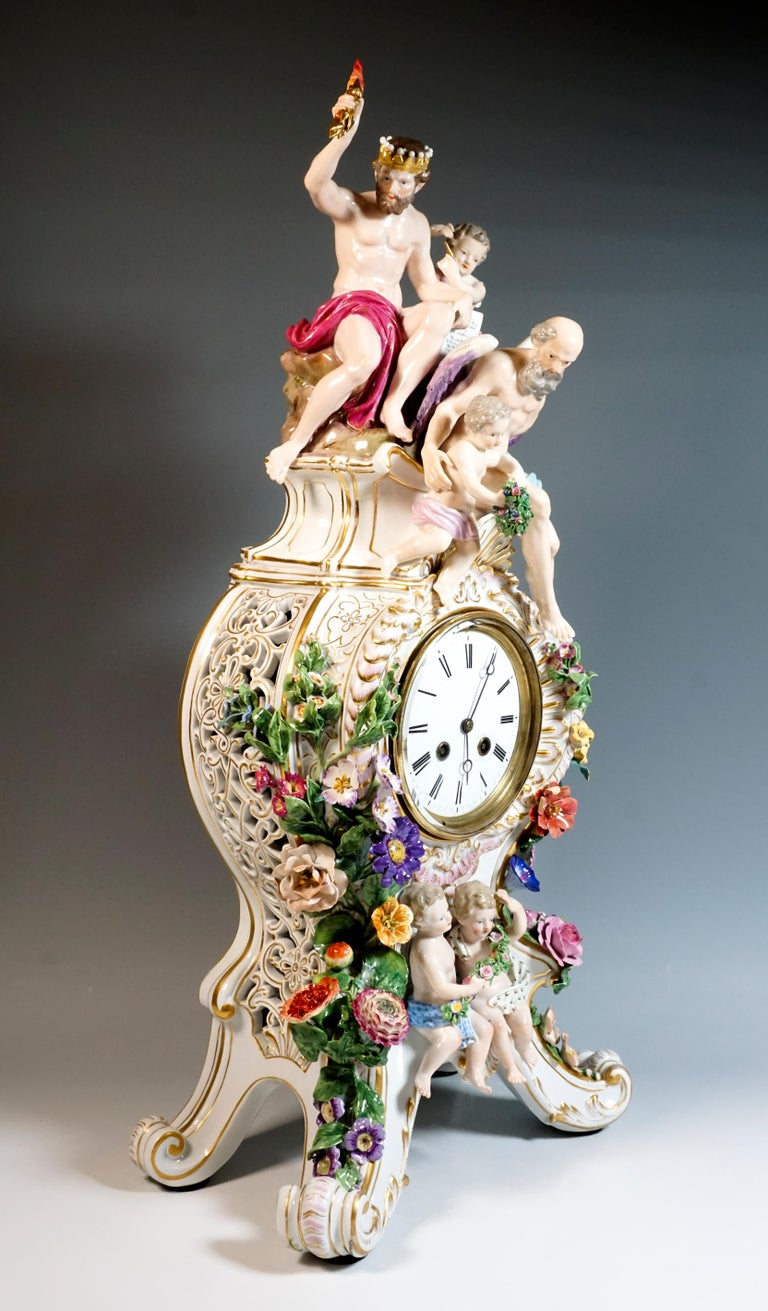 The clock was designed by Leuteritz in the Rococo style using old moulds:  on four raised volute feet with gold rocaille ornamentation rises the clock case, open at the side by a volute and flower breakthrough work, richly decorated with elaborate,