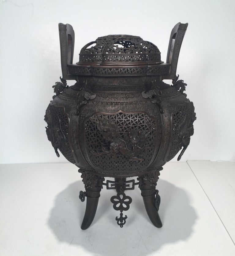 Large Japanese bronze cencer with finely pierced body and lid. The detailed reticulated body with two handles, one handle slightly bent. The bottom with hanging lover ornaments, there are 2 missing ornaments. The finish in the original dark rich