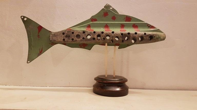 This is a quirky custom made mid-20th century ice fishing decoy that is predominantly lead with metal fins. It has holes bored into it to give it even buoyancy at certain depth and holes for attaching hook lines. It has the original pale green paint