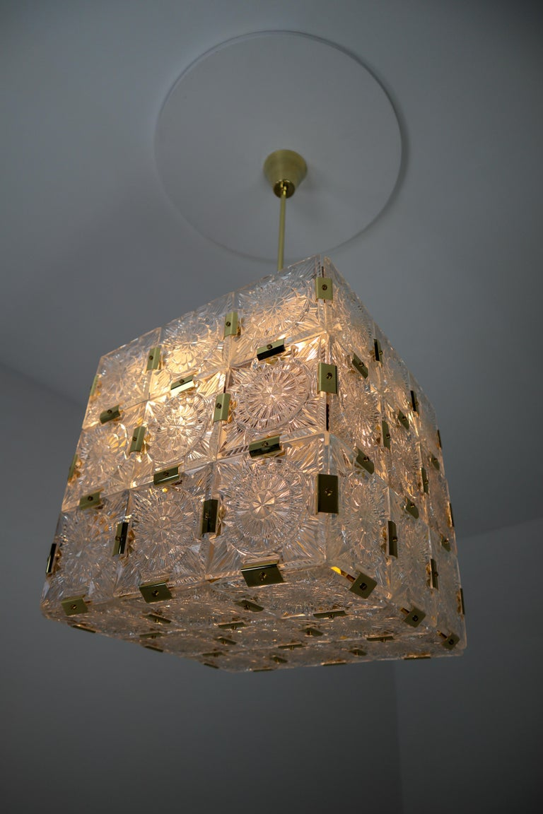 Wonderful and very heavy quality chandelier made in Europe, manufactured, circa 1960s. The chandelier has 4 (E27) sockets and holds 36 large thick geometric cut crystal glass with a brass elements . The sheets beautifully refracting light. This