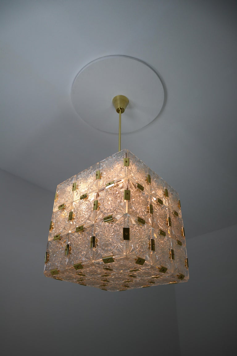 Wonderful and very heavy quality chandelier made in Europe, manufactured circa 1960s. The chandelier has 4 (E27) sockets and holds 36 large thick geometric cut crystal glass with a brass elements . The sheets beautifully refracting light. This