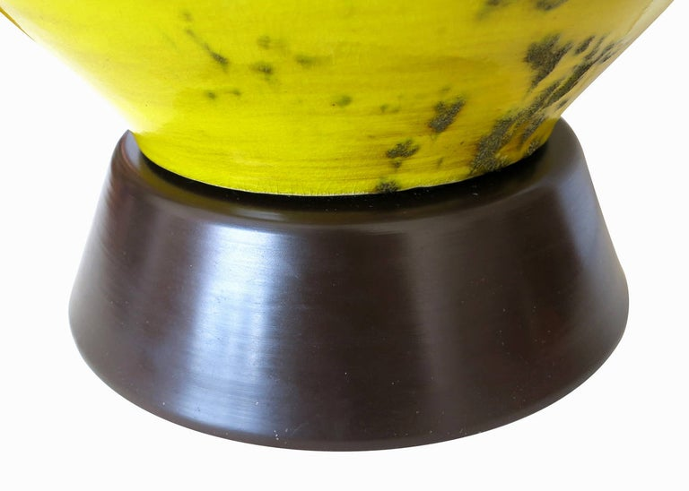 Made circa 1960, the ceramic lamp has a brown and yellow glaze finish that is spotted with textural areas. The lamp is of a unique hourglass shape, sits on a dark stained base and has brass hardware.