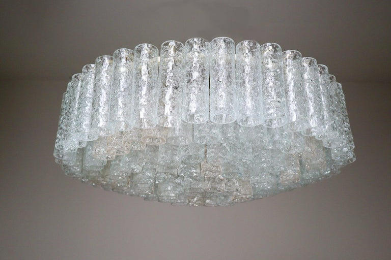 Large 1950s midcentury chandelier was designed by Doria Leuchten, Germany. It features multi-tiered layers of textured ice glass tubes connected to a circular brushed brass frame. The flush mount with 140 glass tubes requires twelve E14 bulbs (40