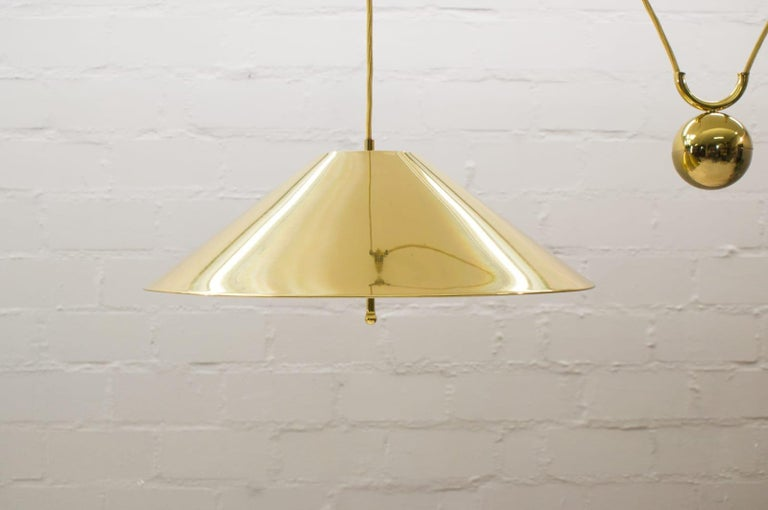 Large pendant lamp designed and manufactured by WKR Leuchten GmbH in Germany in the style of Florian Schultz.   Features a brass shade with a white lacquered interior and a heavy counterweight providing an adjustable height.   Height variable by