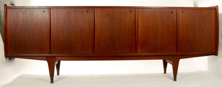 Exceptional Danish modern sideboard credenza of solid teak with four lockable doors, sculpted legs, and brass feet. The doors open to reveal shelved space and spaces with drawers. The case has sculpted sides which extend beyond the doors and top to