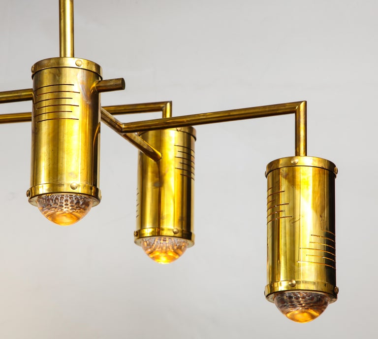 This Italian chandelier is the epitome of midcentury chic. Linear natural brass 9-arm frame features cylinder brass lights on multiple levels. Measures 5 ft. wide. Newly wired for U.S. standards utilizing LED lightbulbs. This chandelier is on