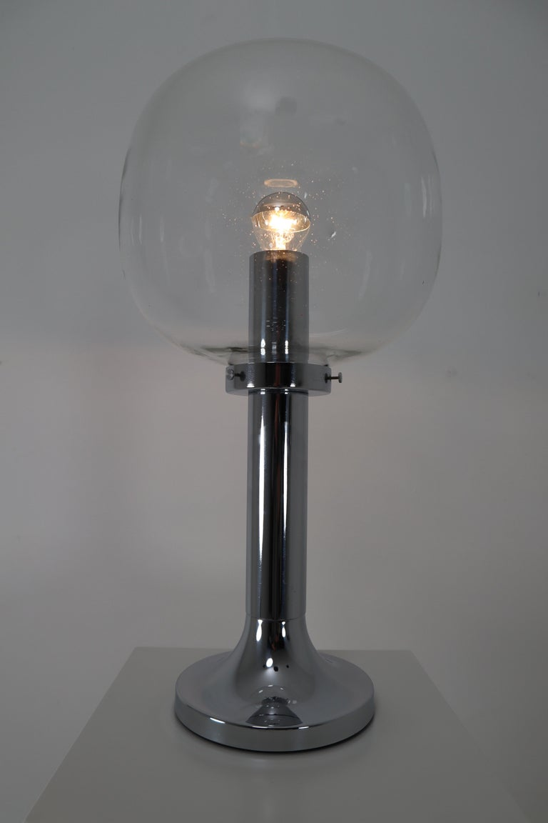 Large Mid-Century Modern chrome table lamp. The hand blown glass globe have a clear tint to them and contain air bubbles of varying sizes and density that create a wonderful light effect. The base is made of solid and chrome-plated metal. One E27