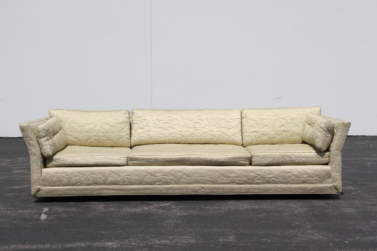 All original Mid-Century Modern custom made sofa by Flair Inc with angled arm detail on brass castors, in need of restoration. This sofa has great bones, shown in original quilted upholstery, which has wear and stains. Structurally solid. Retains