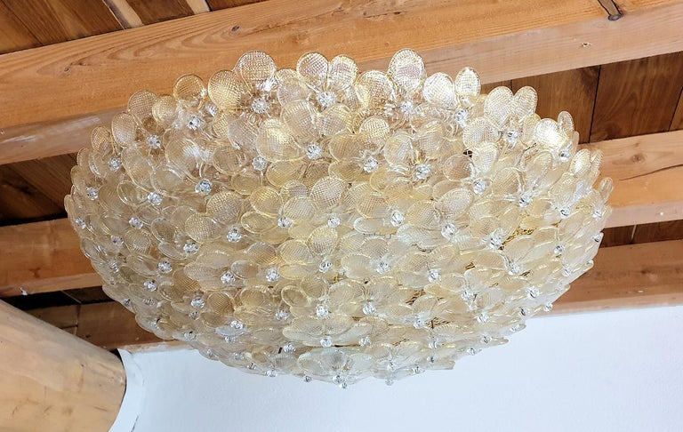 Large round Mid-Century Modern Murano glass flower chandelier, or flushmount ceiling light, by Barovier & Toso, Italy, late 1970s. The Murano glass flowers and clear with some gold flakes. The frame is brass. 6-light, candelabra base sockets,