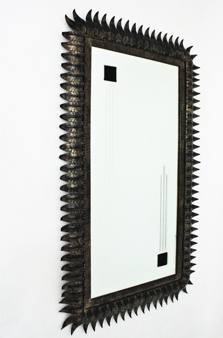Hand-hammered metal leafed rectangular sunburst black patinated mirror with gilded accents, Spain, 1950s. The contrast between the dark iron leafed frame with the parcel-gilt details and its large mirror surface accented by beveled lines and black