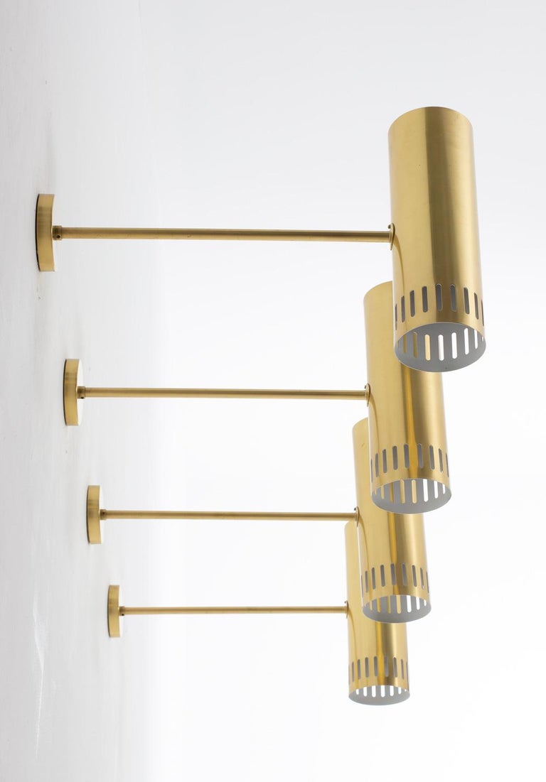 Rare midcentury wall lamps, produced by Boréns, Sweden, circa 1960. These lamps are made of solid, thick brass. They feature one light source, hidden by a cylinder-shaped perforated brass shade. 9 lamps available. Condition: These lamps come from